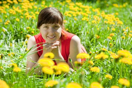 meadow  grass: Mujer joven sonriente que miente en hierba del prado