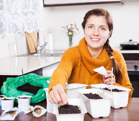 Woman planting seeds in ground at table at home photo