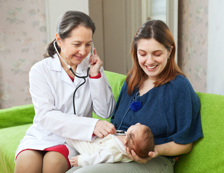 children's doctor: friendly mature childrens doctor examining newborn baby  with  stethoscope Stock Photo
