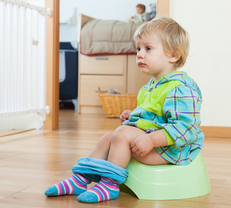 Baby  sitting on green potty in home interior Stock Photo