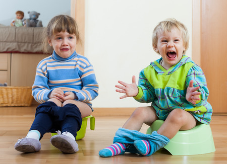 the piss: Two emotional siblings sitting on chamber pots in home interior