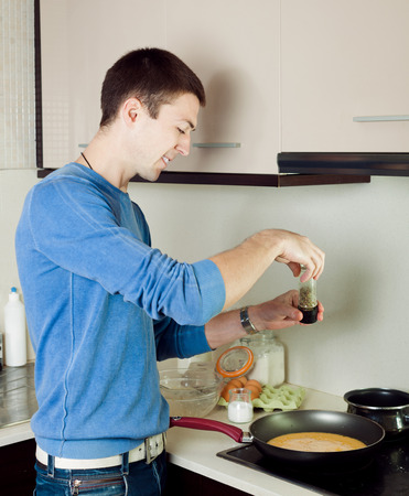 Smiling man cooking omlet in kitchen photo