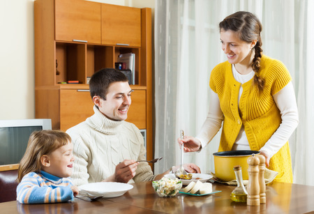 Happy woman serving soup for family in home photo