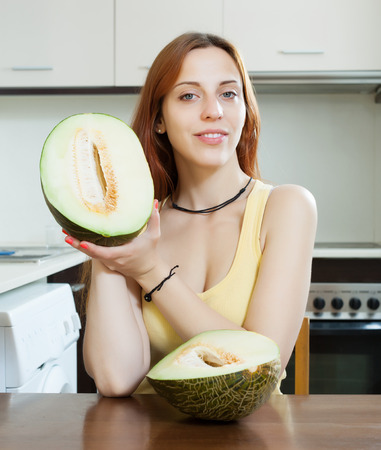 young housewife holding ripe melon at domestic kitchen  photo