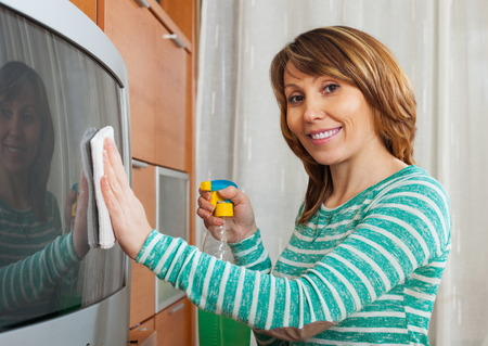 Handsome woman in green cleaning TV at home photo