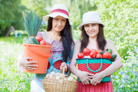 Two happy women with vegetables harvest in garden photo