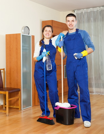 company premises: Two handsome cleaners cleaning floor in room