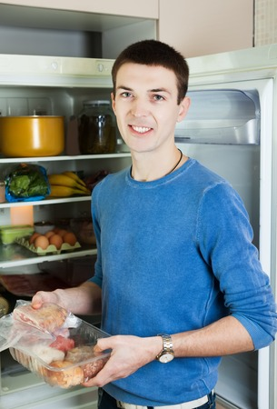 refrigerator kitchen: Handsome guy near opened refrigerator in kitchen at home Stock Photo