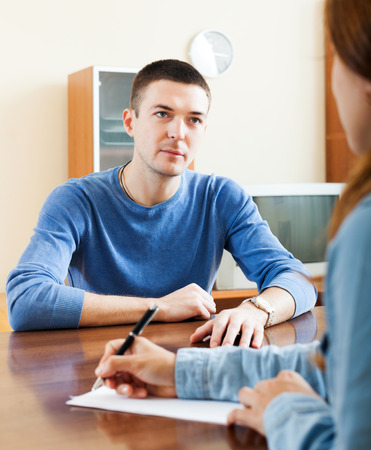 Handsome man an answer questions of social worker in home or office photo