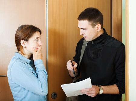 る家のドアで女性から収集するためにしようとしている実業家
