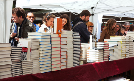 feast day: BARCELONA, SPAIN - APRIL 23: Sant Jordi is Catalan feast day of Saint George. in April 23, 2013 in Barcelona, Spain. Books and red roses traditionally gifts of festival. Focus on books