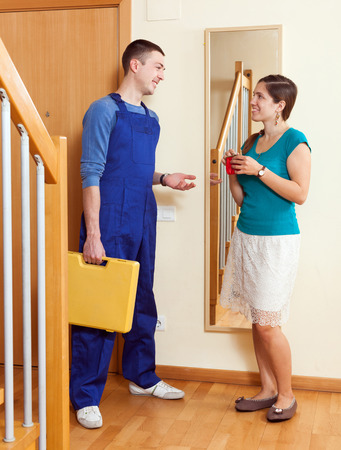 Housewife  meeting  young service worker at the door at home photo