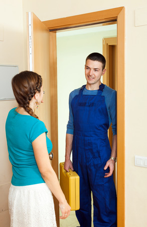 Young housewife  meeting happy repairman  at the door at home photo
