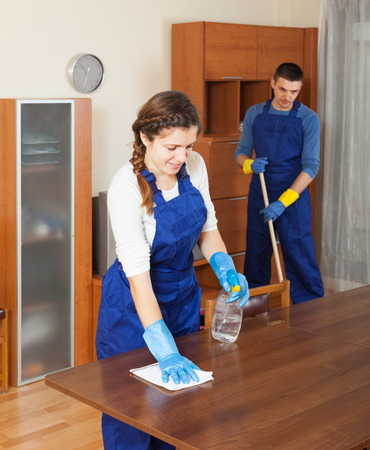 Professional cleaners cleaning furniture and floor in room photo