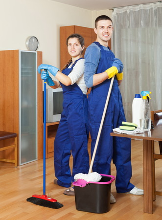 company premises: Two happy cleaners cleaning floor in room