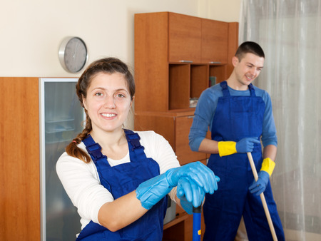 company premises: Cleaning team in uniform is ready to work in room at home Stock Photo