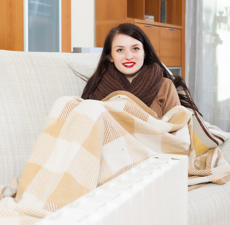 Portrait of   woman warming near electric heater