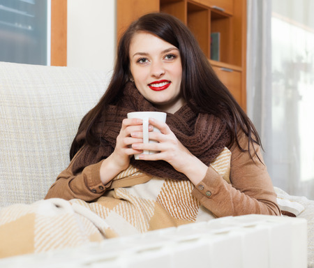 Long-haired girl with cup near calorifer  in home Stock Photo