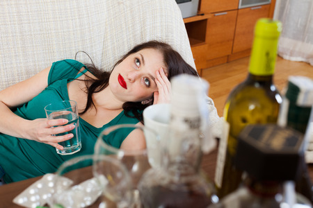Suffering woman with glass of water on sofa