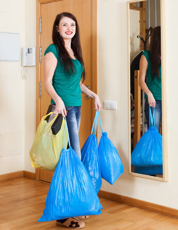 Happy  woman near door with garbage bags at home photo