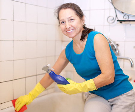 Mature woman cleans bathtub in bathroom at her home photo