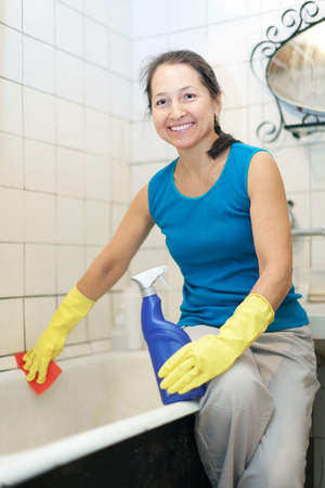 Smiling mature woman cleans bathroom with  cleaner at home photo