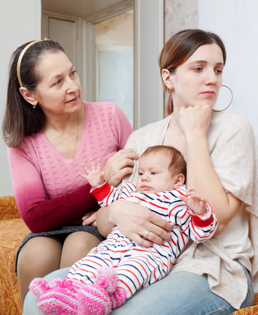 Female family problems. Mature woman comforts crying adult daughter with baby at home photo