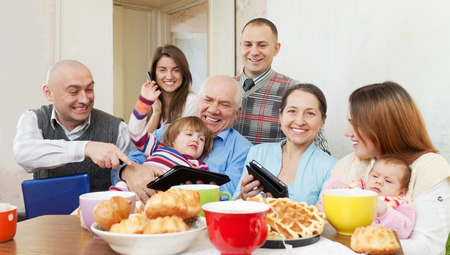 Happy multigeneration family posing together with various electronic communication devices over tea  at home photo