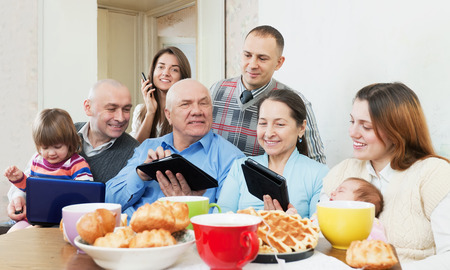 Happy family of three generations or group of friends with electronic devices over tea in living room at home photo