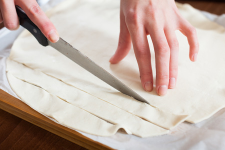 prepack: Close up of hands cutting store-bought dough
