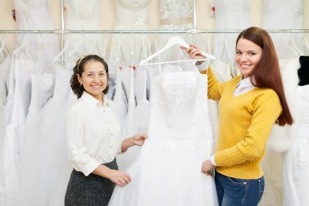 Two women choosing white dress at shop of wedding fashion photo