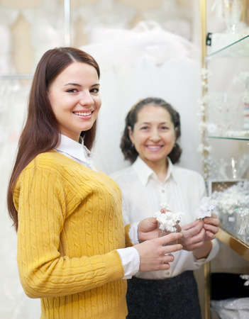 Girl chooses bridal accessories at wedding store. Consultant helps her photo