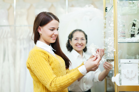 Mature woman helps the girl in choosing bridal accessories at shop of wedding fashion photo