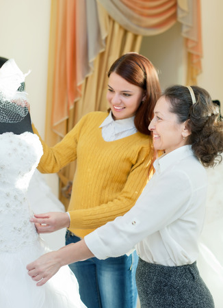 Mature saleswoman helps bride chooses white bridal gown at shop of wedding fashion. Focus on mature photo
