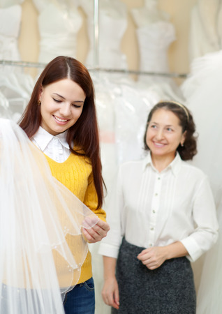 bride chooses bridal veil at shop of wedding fashion. Shop consultant helps her photo