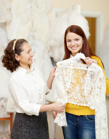 Shop assistant  helps to girl chooses  bridal clothes at shop of wedding fashion photo