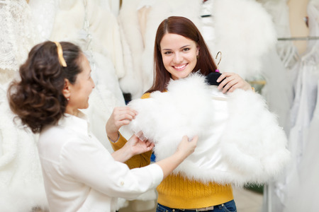 Two happy women chooses fur cape at wedding store. Focus on young bride
