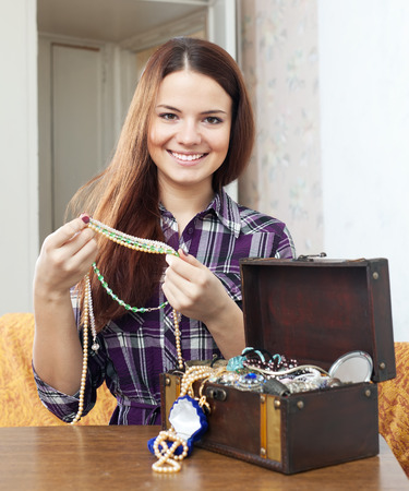ruby house: portrait of pretty woman chooses jewelry in treasure chest