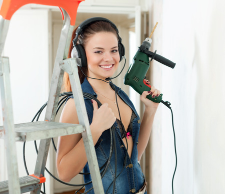 Sexy girl in headphones with drill near stepladder in interior photo