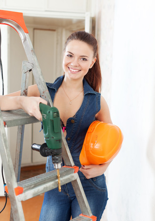 Happy girl with drill and hardhat near stepladder in interior photo