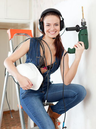 Sexy beauty girl in headphones with drill and hardhat on staircase in interior photo