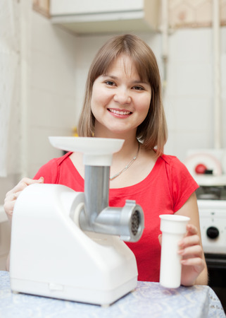 eastward: Young woman with electric sausage meat mincer at home
