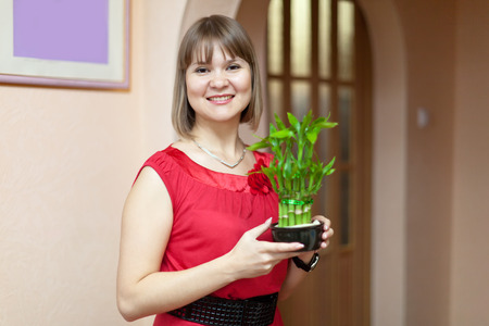 Girl with dracaena in the pot at her home photo