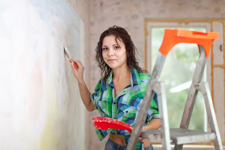 woman paints wall with brush at home photo
