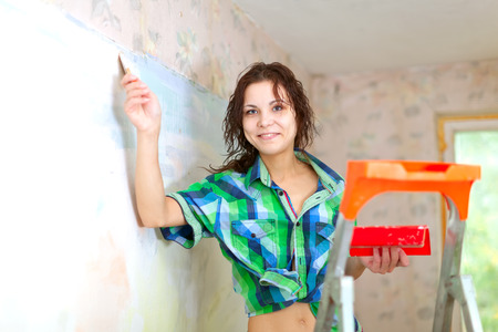 priming brush: Happy woman paints wall with brush at home Stock Photo