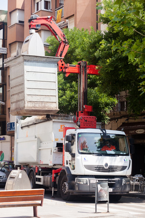 BARCELONA, SPAIN - JUNE 23: Garbage truck collects garbage dumpster in June 23, 2013 in Barcelona, Spain.   Recycling truck picking up bin