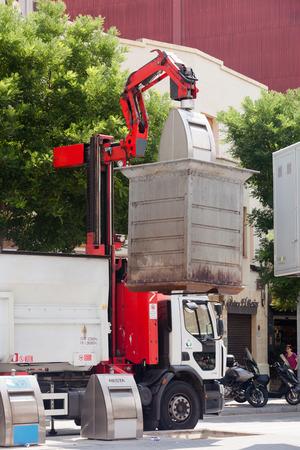 recolector de basura: BARCELONA, CATALUÑA - 23 de junio: Camión de basura recoge latas de basura el 23 de junio de 2013, de Barcelona, ??Cataluña. Camión de reciclaje recogiendo bin