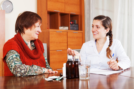 prescribing: happy female doctor prescribing medication to mature woman at home. Focus on patient Stock Photo
