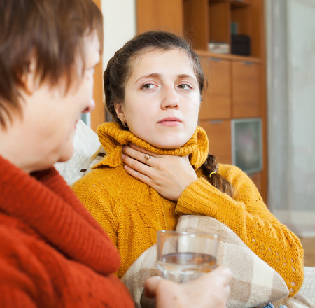nosotrophy: Woman giving glass of water to unwell friend in home