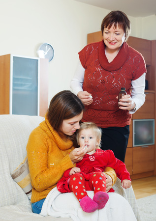 Young mother with mature grandmother giving  medicament to unwell baby  at home photo